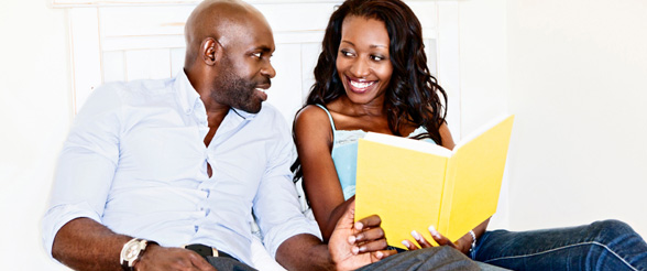 couple smiling reading book together