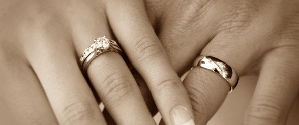 Couple holding hands with their wedding rings displayed